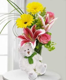 White bear in front of a vased arrangement of yellow and pink flowers