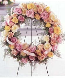 All-rose sympathy wreath in shades of pink and peach.
