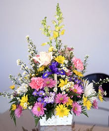 Basket of roses, daisies and other colorful mixed flowers.