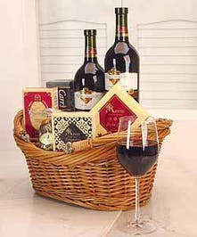 Gift basket filled with two bottles of red wine and assorted cheeses