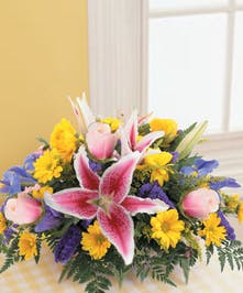 Centerpiece featuring fresh cut lilies, roses, daisies and iris.