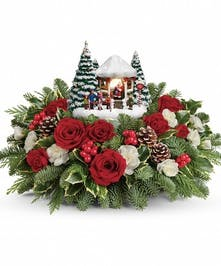 Bouquet of red roses, white carnations, holly and fir surrounding a Thomas Kinkade keepsake.