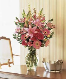 A variety of pink flowers in a clear glass vase.