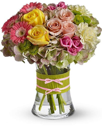 Roses, gerberas and hydrangea in a clear glass vase tied with ribbon and raffia.