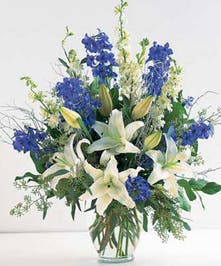 Blue and white flowers in a clear glass vase.