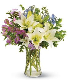 White lilies, blue delphinium, and purple and green blossoms in a clear glass vase.