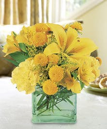 Mint glass cube vase holds yellow flowers and greenery.