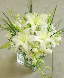 White lilies, hydrangea, orchids and roses in a clear glass cube vase