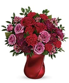 Red and pink roses, carnations and waxflower with greenery in a twisted red ceramic vase.