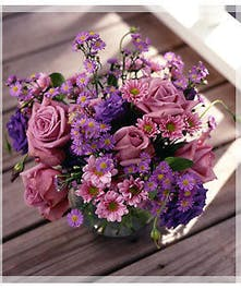 Purple flowers in a clear glass bubble bowl vase.