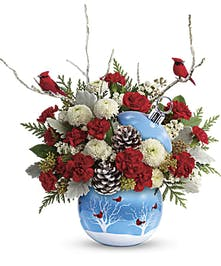Keepsake ceramic ornament designed with red cardinals in the snow, filled with red and white flowers and winter greenery