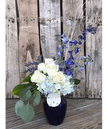 Blue delphinium, white hydrangea and white roses in a sapphire blue vase with sand dollar accent.