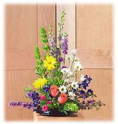 Traditional sympathy presentation of roses, daisies, bells of Ireland liatris and more.