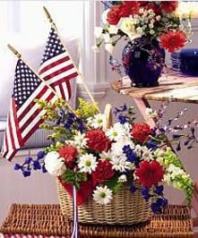 Wicker basket filled with red, white and blue flowers with American flag accents.