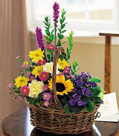 African violets, sunflowers and more in a charming wicker basket.