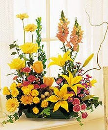 Artful presentation of gerberas, carnations, lilies, roses, snapdragons and ivy with a bird's nest decoration.