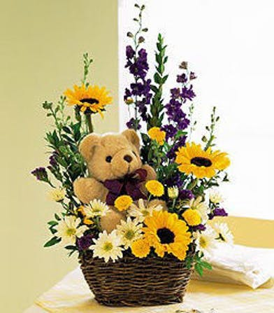 Basket of flowers with plush teddy bear.