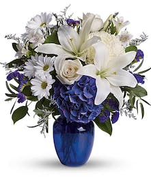 Blue and white flowers in a cobalt blue glass vase.