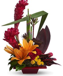 Lilies, tropical red ti leaves and red ginger in a decorative bamboo planter.