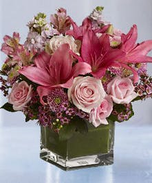 Pastel pink bouquet in a glass cube vase.
