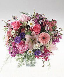 Roses, gerbera, dendrobium orchids, and more arranged in a clear glass vase.