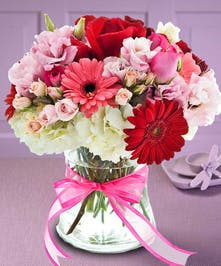 Red, pink and white flowers in a clear glass vase tied with a pink ribbon.