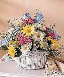 An assortment of flowers in a woven basket with a gingham bow.