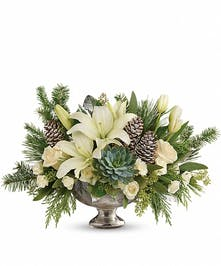 Holiday centerpiece of green and white flowers, succulents and more in a mercury glass bowl.