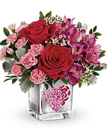 Red roses, pink roses, carnations, waxflower and dusty miller in a glass cube vase with pink heart decoration.