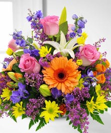 Bright spring centerpiece of pink, orange, purple and yellow flowers.