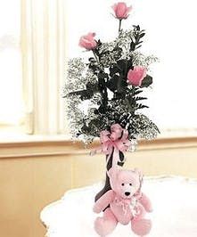 Three pink roses in a bud vase with a pink plush teddy bear.