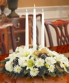Winter centerpiece of all-white flowers, greenery and taper candles