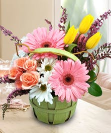 Pink, yellow and white flowers in a green handbasket.