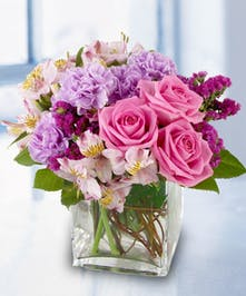 Pink and purple pastel flowers in a glass cube vase.