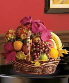 Gift basket filled with assorted fresh fruit and a chrysanthemum plant.