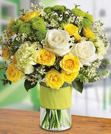 Yellow, white and green flowers in a cylinder vase tied with green ribbon.