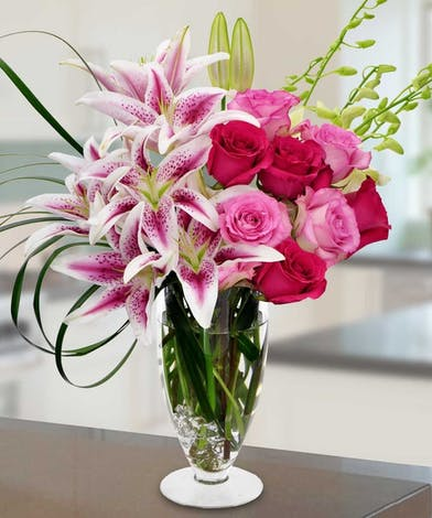Pedestal vase filled with lilies, roses and orchids