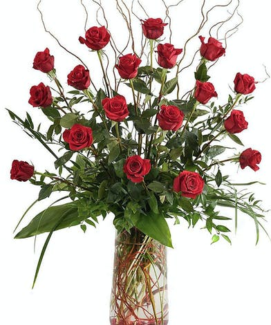 Red roses, greenery and curly willow in a clear glass vase.