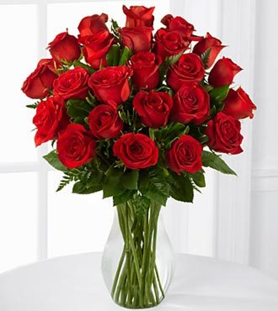 Two dozen long-stemmed red roses in a clear glass vase.