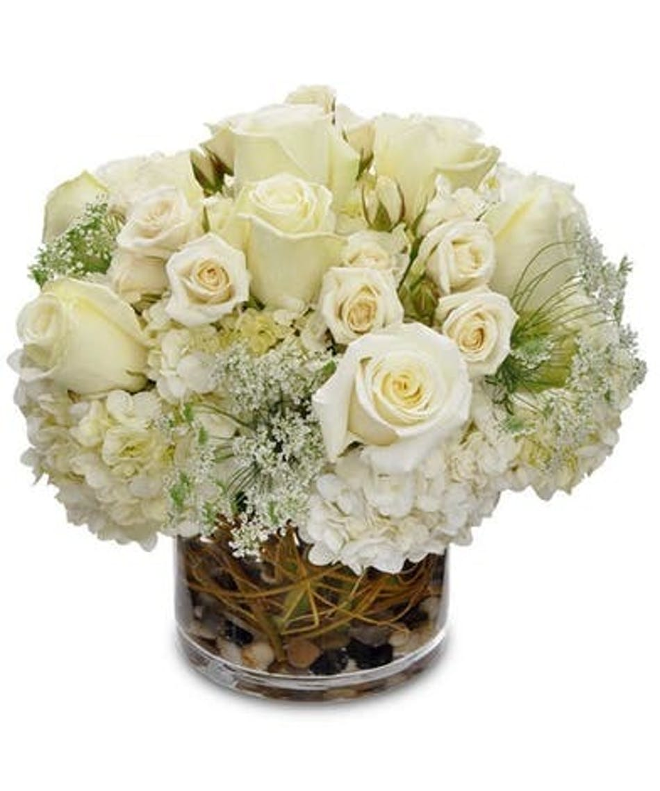 All-white bouquet of flowers in a clear glass vase.
